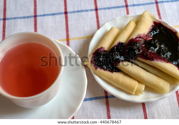 pancakes with jam and a Cup of red tea