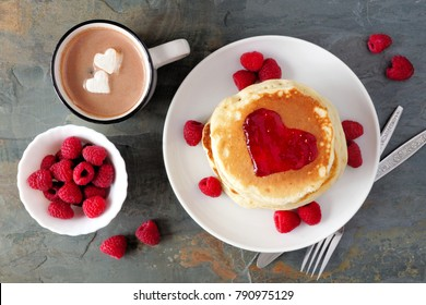 Pancakes with jam in shape of heart, hot chocolate and raspberries over a slate background. Love concept.