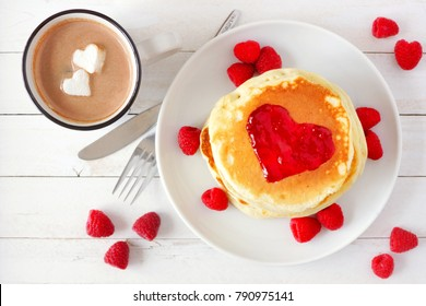 Pancakes with jam in shape of heart and hot chocolate with marshmallow hearts over a white wood table. Love concept.
