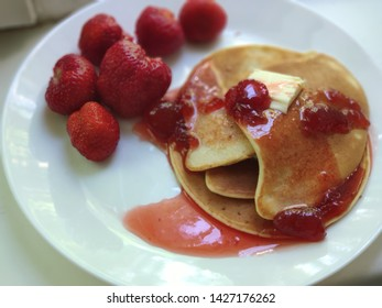 Pancakes with jam and strawberries on white plate closeup, soft focus