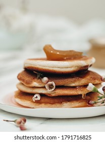 Pancakes lie on top of each other, white flowers between them. Poured apricot jam on top. light background. Delicious and hearty breakfast. Fruity vzhem. Flowers and food.