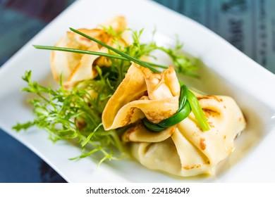 pancakes with meat decorated green onions on a white plate