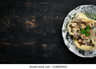 Pancakes with mushrooms, cheese and cream sauce. On a wooden background. Top view. Free space for your text.