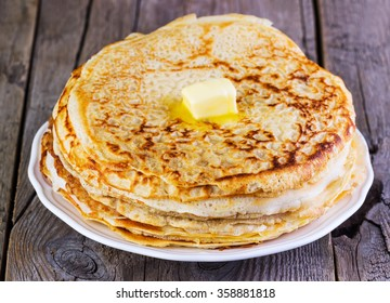 pancakes with oil on a wooden background