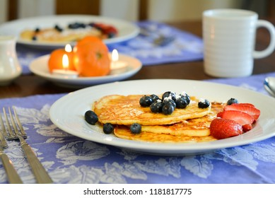 Pancakes on a breakfast table with blueberries and strawberries.