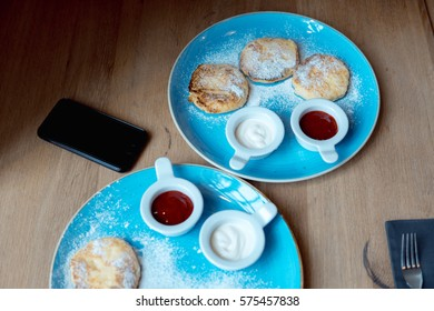 pancakes on a plate with red jam and cream