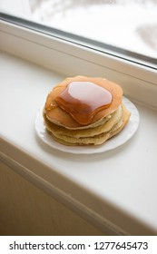 Pancakes are on a plate on the windowsill.
