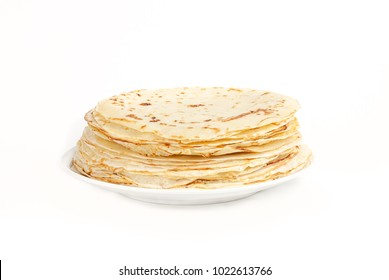 Pancakes on a saucer on a kitchen towel. Many pancakes are stacked. Thin pancakes with crispy crust. Maslenitsa. Pancakes for breakfast and carnival. Food background