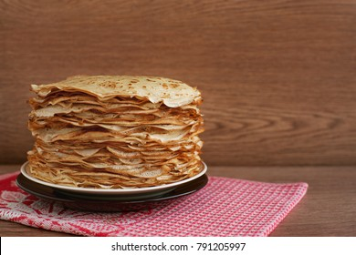 Pancakes on a saucer on a kitchen towel. Many pancakes are stacked. Thin pancakes with crispy crust. Maslenitsa. Pancakes for breakfast and carnival.