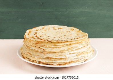 Pancakes on the white plate.  Many pancakes are stacked. Thin pancakes with crispy crust. Maslenitsa. Pancakes for breakfast and carnival. Food background.