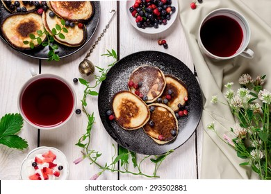 Pancakes on white wooden table decorated with flowers and berries. Selective focus.