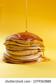 pancakes on a yellow background. poured with honey or syrup