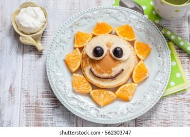 Pancakes with orange, grape and banana for kids
