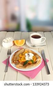 Pancakes with orange on bright background