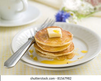 Pancakes with pat of melted butter on top and coffee in the background. Selective focus