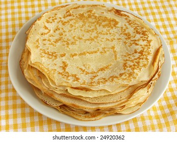 pancakes pile on yellow checker tablecloth