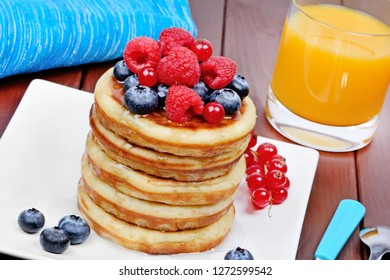 Pancakes in a plate with berries and orange juice on wooden table