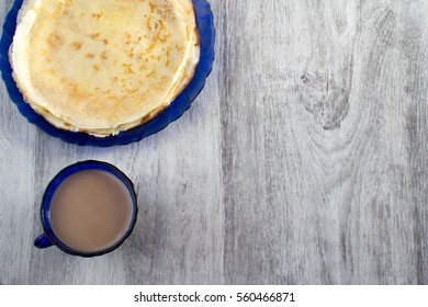 Pancakes in plate and cup of coffee on wooden table. Top view. Flat lay.