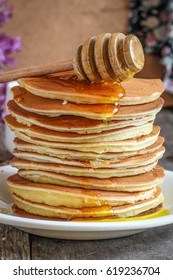 Pancakes in a plate on a wooden surface