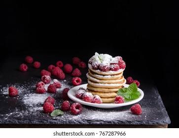 Pancakes with raspberries around on black backgound