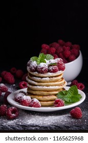 Pancakes with raspberries on black backgound