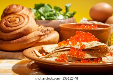 Pancakes with red caviar and greens