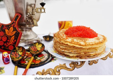 Pancakes with red caviar on the background of samovar and wooden dishes in Khokhloma style.