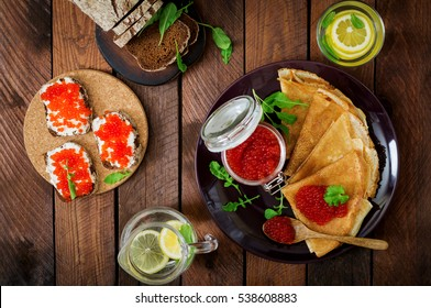 Pancakes with red caviar on plate. Sandwich with red caviar. Russian cuisine. Top view. Flat lay. Maslenitsa