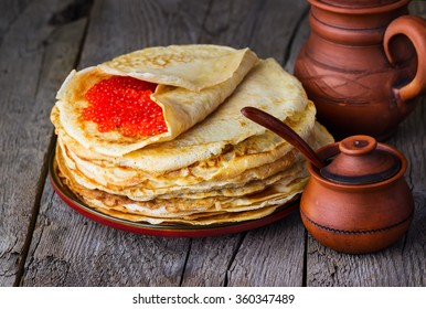 pancakes with red caviar on a wooden background