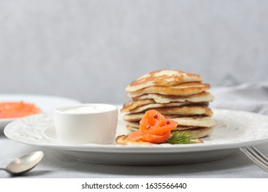 Pancakes with salted salmon.  Fritters served with salmon and sour cream.  Cutlery and a napkin complete the table.  Light background.  Close-up.