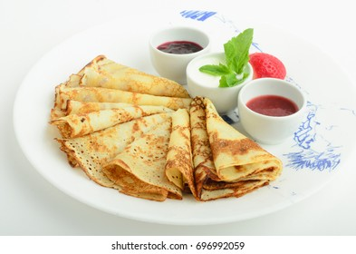 Pancakes with sauces decorated strawberry and mint on a plate isolated on white background