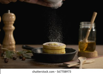 Pancakes served  in black ceramic pan topped with sugar icing, butter and maple syrup on old wooden table.