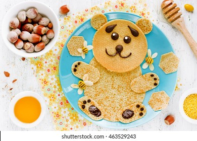 Pancakes in the shape of cute bear with honey and nuts for kids breakfast, funny food art idea for children top view
