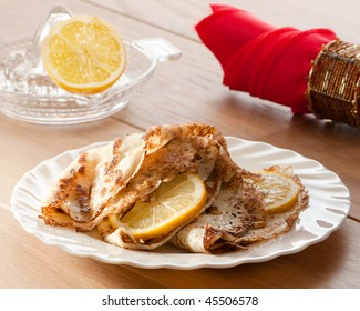 Pancakes for Shrove tuesday with lemon slices, napkin in background
