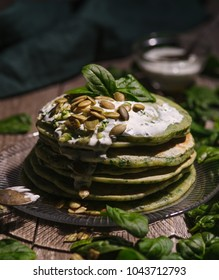 Pancakes with spinach and pumpkin seeds on a wooden table. Country style.