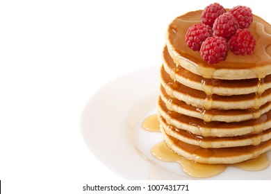 Pancakes Stack with maple syrup and raspberries isolated on a white background. Family Breakfast. Brunch. Shrove Tuesday. Mardi Gras. Snacks. Sweets. Food. Dessert.