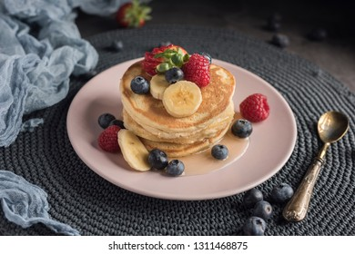 Pancakes with strawberries, raspberries, blueberries, banana and syrup on a pink plate. Horizontal