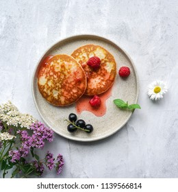 Pancakes with sweet jam, fresh berries and mint leaves on concrete table. Top view.