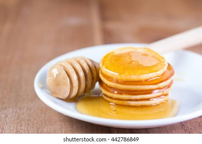 Pancakes in syrup on wood background