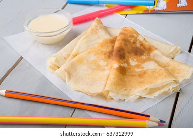 Pancakes with syrup on wooden board among the pencils