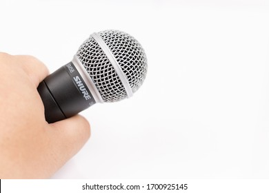 Pancevo, Serbia - 04/11/2020: Shure SM58 Microphone in the hand isolated above white background.