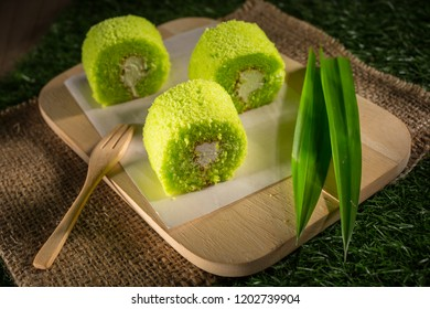 Pandan cream roll cake, Homemade bakery pastry on wooden tray, Sponge roulades with cream and fresh Pandan leafs, selective focus, copy space