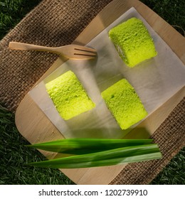 Pandan cream roll cake, Homemade bakery on wooden background, Sponge roulades with cream and fresh Pandan leafs, selective focus, copy space