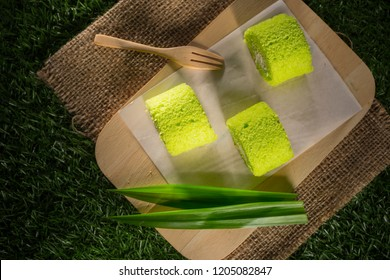 Pandan cream roll cake, Homemade bakery on wooden background, Sponge roulades with cream and fresh Pandan leaves, selective focus, copy space