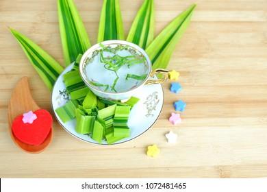 Pandan juice and Pandan leaf,Pandan juice in glass and Pandan healthy drink water on table wood.