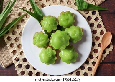 Pandan Pancake - Thai dessert made from pandan, flour, coconut milk and sugar : In Thai called Kanom Krok Bai Toey or Kanom Krok Singapare at top view on wooden background - Shutterstock ID 1956155179