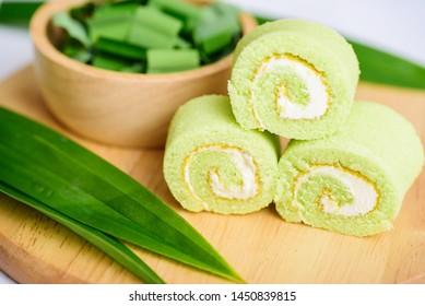 Pandan roll cake and fresh pandan leaf on wooden