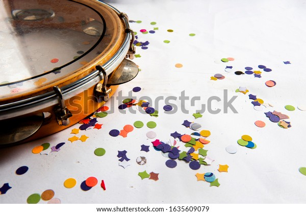 Pandeiro, traditional samba instrument, used in the Brazilian carnival. White background, paper confetti. Seen from above. Space for text. Horizontal.