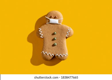 Pandemic Christmas. Celebration restriction. Coronavirus winter holidays protective measures. New normal. Brown gingerbread man in medical face mask alone isolated on orange copy space background. - Shutterstock ID 1838477665