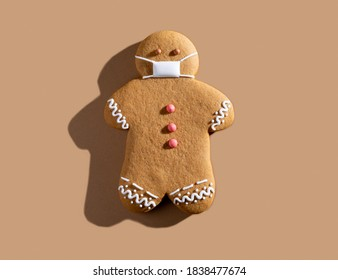 Pandemic Christmas. Quarantine celebration. Covid-19 winter holidays safety. New normal. Brown gingerbread man in protective face mask alone isolated on beige background. - Shutterstock ID 1838477674